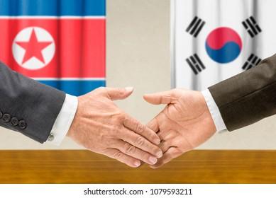 Representatives of North Korea and South Korea shake hands