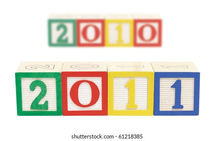 Representing the change to a new year, wooden alphabet blocks in the foreground form '2011'.  Out of focus in background, are a row of blocks form '2010' representing the old year. Isolated on white.