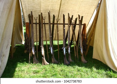 Reproduction vintage muskets standing in the tent at a military camp. The infantrymen light guns on the historical reenactment festival in Western Ukraine. Living history event. Musketeers' weapon