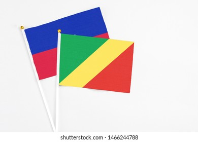 Republic Of The Congo and Haiti stick flags on white background. High quality fabric, miniature national flag. Peaceful global concept.White floor for copy space.