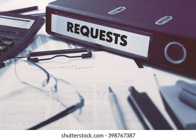 Requests - Office Folder on Background of Working Table with Stationery, Glasses, Reports. Business Concept on Blurred Background. Toned Image.