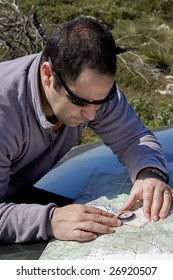 A rescue crew member using a field map and a compass to orienteering