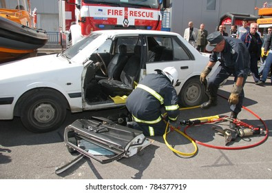 Rescue firefighter in action for saving people from a car crash in front of other people in Sofia, Bulgaria - Sep,11, 2007.