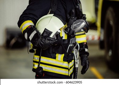 Rescue firefighter in safe helmet and uniform standing by car