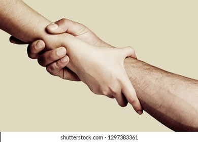 Rescue, helping gesture or hands. Strong hold. Close-up. Two hands, helping hand of a friend. Handshake, arms, friendship. Friendly handshake, friends greeting, teamwork, friendship.           - Image