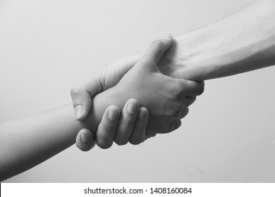 Rescue, helping gesture or hands. Strong hold. Close-up. Two hands, helping hand of a friend. Handshake, arms, friendship. Friendly handshake, friends greeting, teamwork, friendship