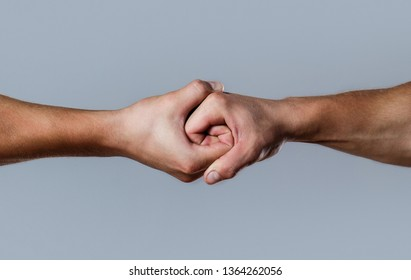 Rescue, helping hand. Male hand united in handshake. Man help hands, guardianship, protection. Two hands, isolated arm, helping hand of a friend. Friendly handshake, friends greeting.