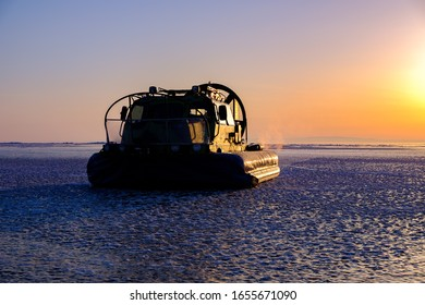 Rescue hovercraft boat on the surface of frozen lake Baikal in sunrise