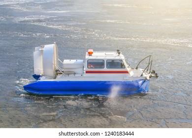 Rescue hovercraft crosses the melting ice illuminated by sunlight (toned)