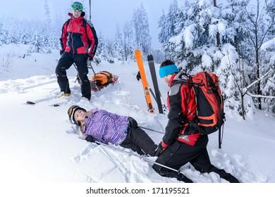 Rescue ski patrol help injured woman skier lying in snow
