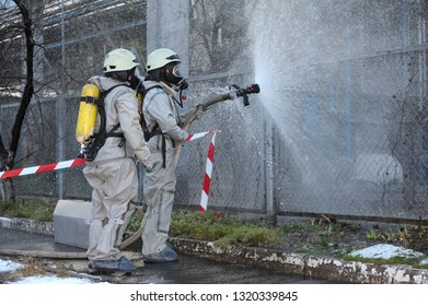 Rescue team training of chemical decontamination: rescuers in protective ensembles watering plant territory with syringe. February 21,2019. Kiev, Ukraine