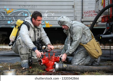 Rescue team training of chemical decontamination: rescuer in a protective ensemble turning a valve of a fire hydrant to water plant territory. February 21, 2019. Kiev, Ukraine