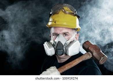 A rescue worker wears a respirator in a smokey, toxic atmosphere carrying a sledgehammer.