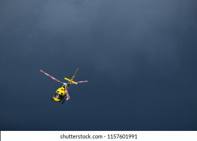 A rescue Yellow helicopter flying. A dark blue background. bad weather