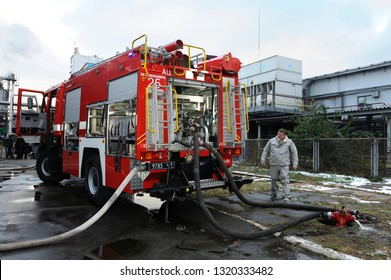 Rescuer team training chemical decontamination: fire truck parked, hoses attached to hydrants, factory facility on a background. February 21,2019. Kiev, Ukraine