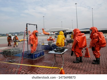 Rescuers in protective suits go through a decontamination shower during an emergency exercise at Subang Airport near Kuala Lumpur, Malaysia, 25 July 2019