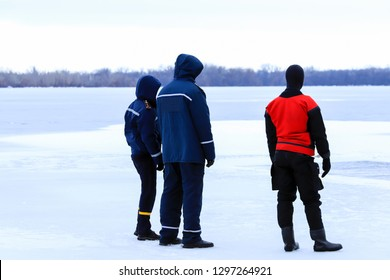 Rescuers in uniform and diving suit are on duty on the ice of a frozen river during winter fishing and sport events. Rescue service on the Dnieper River, Dnipro city, Ukraine, Dnepropetrovsk