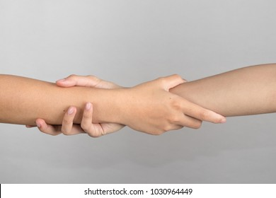 Rescuing and helping by holding or gripping the forearm.Hand and arm pulling up. The Concept of help, love, friendship, support, teamwork, partnership, reaching, couple.