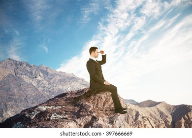 Research concept with businessman sitting on mountain top, looking into the distance on clear sky background
