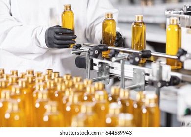 Research and development concept. Hands of professional worker of factory putting glass bottles with yellow liquid on conveyor line. Automated process of producing cosmetic products on factory