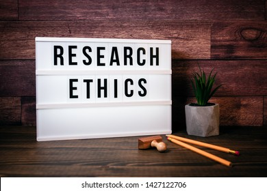 Research Ethics. Text in lightbox. Wooden office table