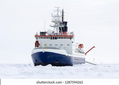 Research icebreaker docked over an ice floe in Antarctica