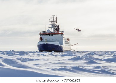 Research icebreaker and a helicopter while setting up an ice camp