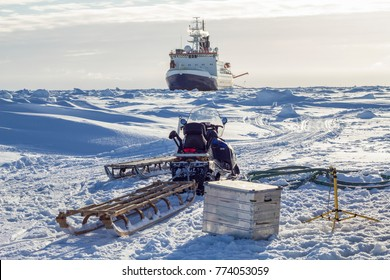 Research icebreaker and snowmobile with sledges while setting up an ice camp