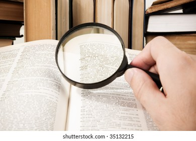 research (selective focus on some words of dictionary (center of magnifying glass))
