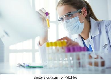 Forscher, Arzt, Wissenschaftler oder Laborassistent, der mit medizinischen Tuschlöhren aus Kunststoff im modernen Labor oder Krankenhaus arbeitet