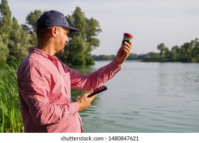 researcher ecologist with tablet examines tube with green algae outside