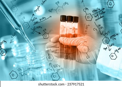 Researcher is holding the test tube, with chemical equations background, in laboratory