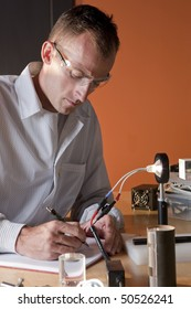 A researcher in a lab coat and goggles, making notes on an experiment. He is surrounded by scientific equipment. Vertical format.