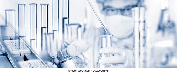 Researcher with pipette and glass flask and many other laboratory utensils