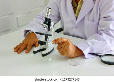 the researcher in white suit with misroscope and looking microscopic sample in his hand