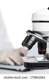 Researcher working on laptop behind microscope