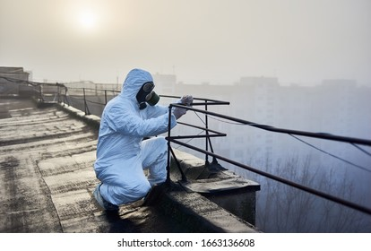 Researcher is working with a railing on the roof in the morning, wearing protective clothing and gas mask. Concept of environmental problem and air pollution