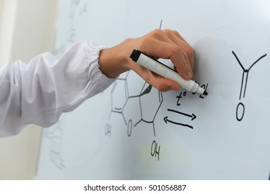 The researcher writes a chemical formula on a white board