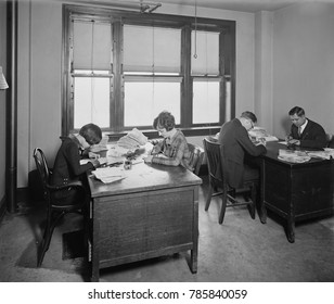 Researchers at the National Bureau of Identification, which became part of the FBI in 1924. Men and women examining fingerprints with magnifying loupes
