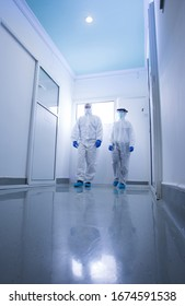 Researchers in protective clothing walking through laboratory hall. Viruses, diseases and biohazard safety concept