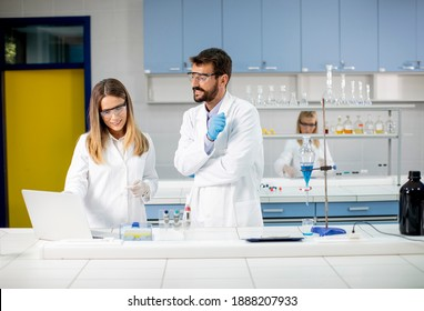 Researchers working with blue liquid at separatory funnel in the laboratory