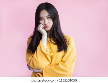 Resentment, boredom, pouting lips. Boring, dull face. Offended girl looks with sadness and is ready to cry. Pink background, yellow sweetshot, standing leaning on the arm