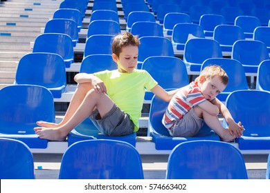 resentment and compromise. quarreled children sit facing away from each other. the older boy are attempting to reconcile. the concept of the peace-making