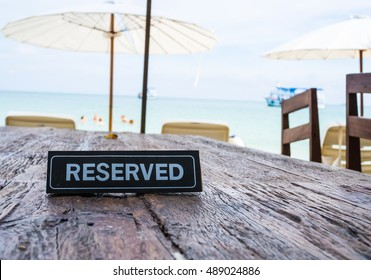Reserved banner on restaurant table, beach background