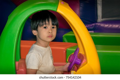 Reserved and Introverted Asian Boy Sits in a Colorful Toy Car in the Playground