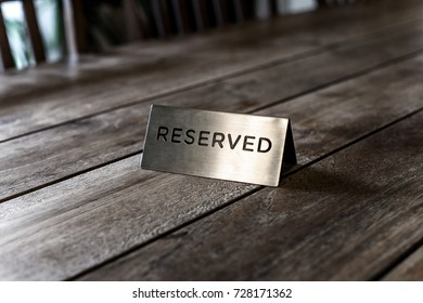 Reserved Metal Plate on the wooden Table. Reservation Seat at restuarant.