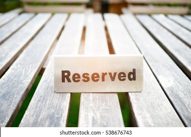 Reserved metal plate is set on wooden table to inform that this table has been booked for lunch or dinner.