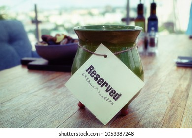 Reserved sign on restaurant table, outdoor summer terrace, toned image, soft grained effect