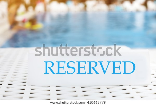 Reserved sign on the summer pool background. Vacation concept