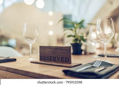Reserved sign on table in modern light restaurant. Romantic dinner settings.